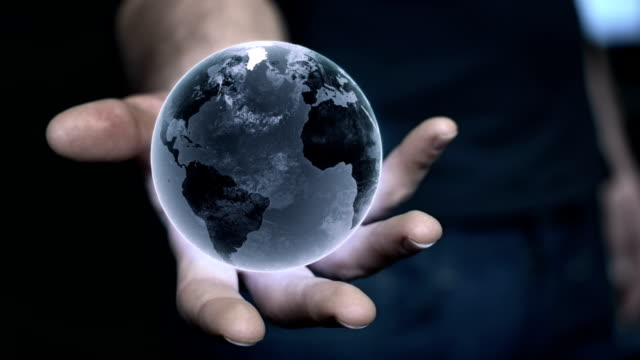 man holding earth model in his hand. globalization metaphor - holographic stock videos and b-roll footage
