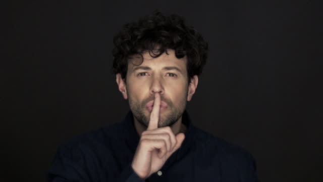man holding finger to lips in silence - only men stock videos & royalty-free footage