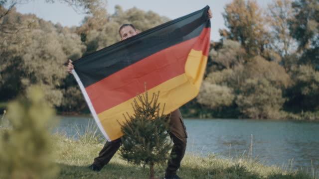man holding tyskland flagga! - banderoll bildbanksvideor och videomaterial från bakom kulisserna