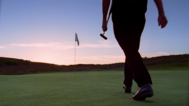 vídeos y material grabado en eventos de stock de man holding golf club picking up golf flag on golf course at dawn - bandera de golf