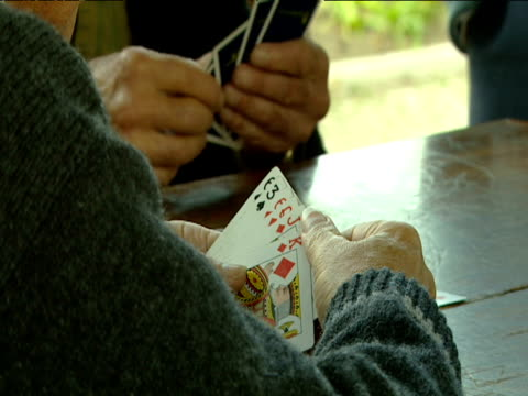 Man holding hand of cards picks out three of spades and places it on table.