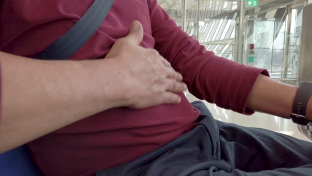 4k man holding hands over stomach . - fat stock videos & royalty-free footage