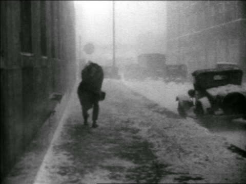 b/w 1939 man holding hat while walking in windy snowstorm on city sidewalk / educational - 1930 1939 video stock e b–roll