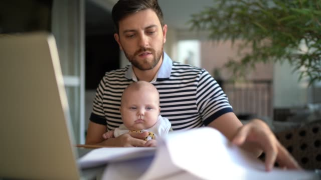 man holding his newborn son and working with laptop at home - responsibility stock videos & royalty-free footage