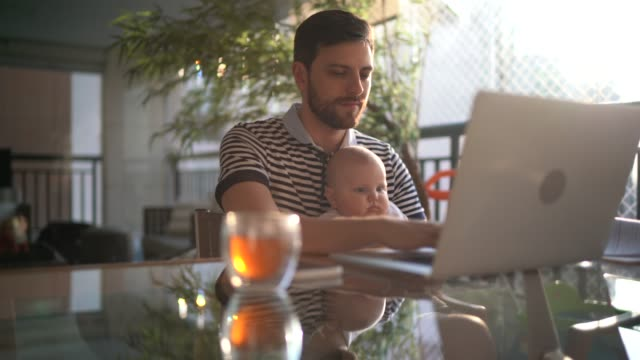 man holding his newborn son and working with laptop at home - economy stock videos & royalty-free footage