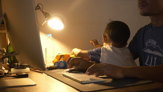 stockvideo's en b-roll-footage met man holding his son and working with computer at home - elektrische lamp
