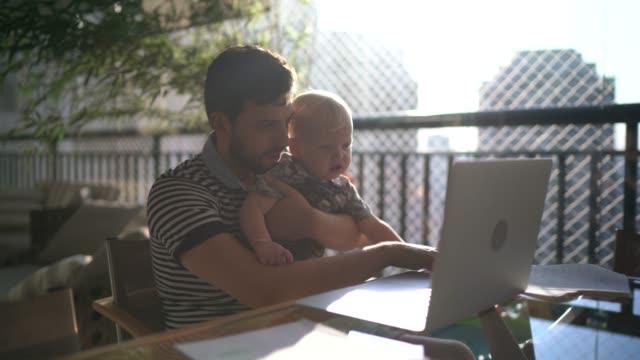 vídeos y material grabado en eventos de stock de hombre sosteniendo a su hijo y trabajando con la computadora portátil en casa - padres amos de casa