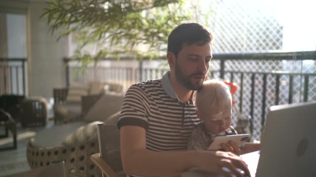 man holding his son and working with laptop at home - candid stock videos & royalty-free footage