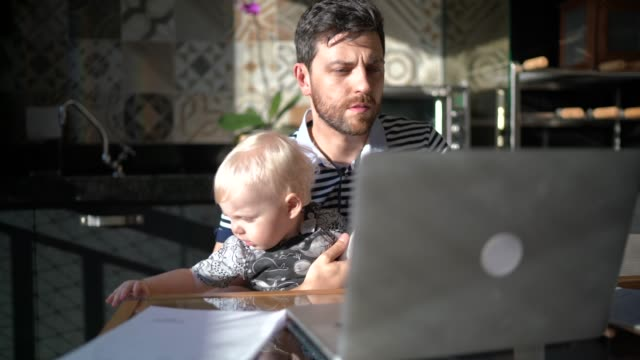 vídeos de stock e filmes b-roll de man holding his son and working with laptop at home - multitarefas