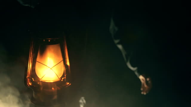 man holding kerosene lamp in dark night - electric lamp stock videos & royalty-free footage