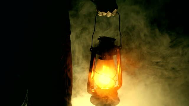 vidéos et rushes de homme tenant la lampe à pétrole dans la nuit noire - kérosène