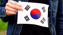 Man holding Korean flag outdoors. Independence Day, or national holidays concepts