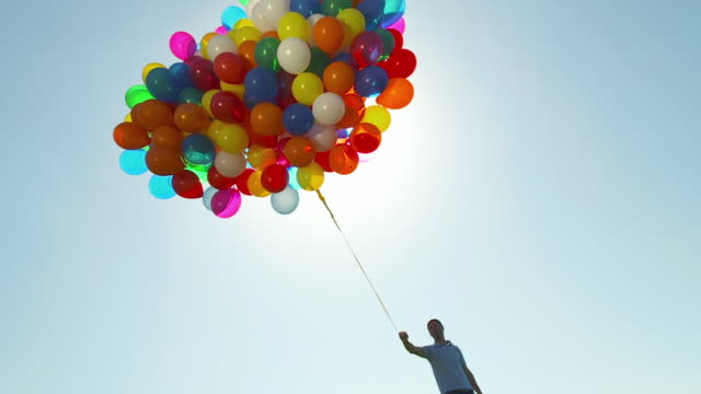 WS man holding large bunch of balloons against sun and walking away