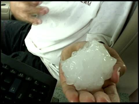CU Man holding large hail stone to camera, USA