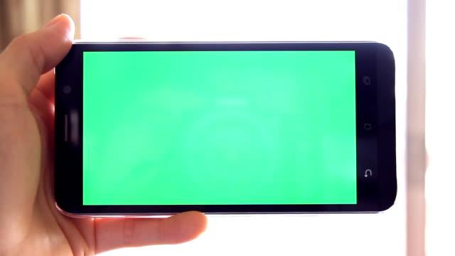 vídeos de stock, filmes e b-roll de homem que prende o telefone móvel com a tela verde na cena interna da posição horizontal-home - visor digital