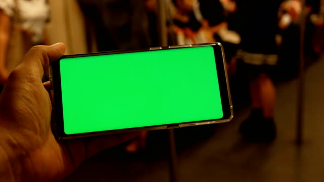 vídeos de stock e filmes b-roll de man holding mobile phone with green screen on the train - horizontal