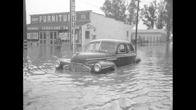 vidéos et rushes de man holding movie camera stands in floodwater shooting footage, flooded commercial building in background / two men pulling car through floodwater... - équipement audiovisuel