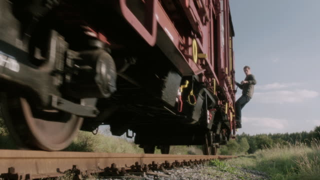 pan man holding on to the exterior of last train car then jumping off - formato panoramico con bande nere video stock e b–roll
