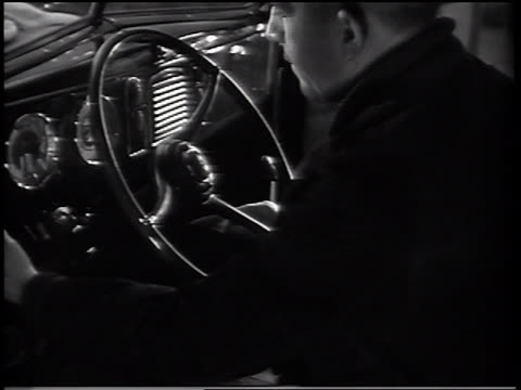 B/W 1937 man holding onto steering wheel of 1938 Ford V-8 car / commercial