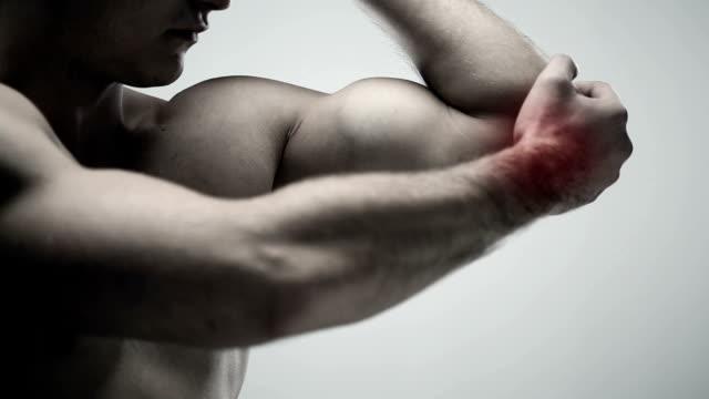 vídeos de stock, filmes e b-roll de homem segurando o dedo cotovelo - músculo humano