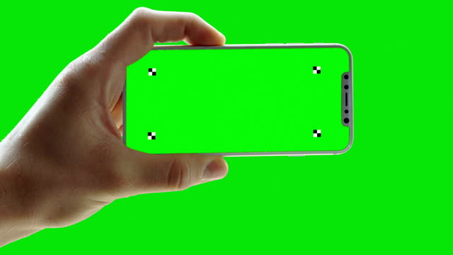 vídeos de stock e filmes b-roll de man holding phone on green screen. trackers - horizontal