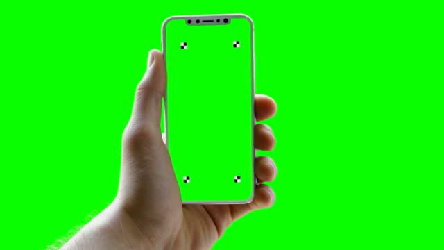 man holding phone on green screen. trackers - green background stock videos & royalty-free footage