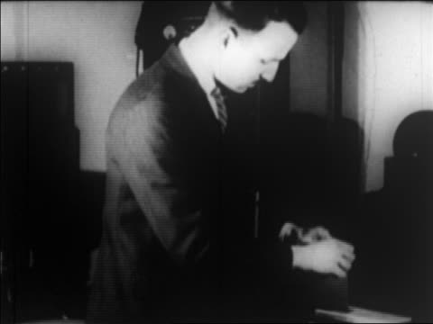 vidéos et rushes de b/w 1924 man holding photograph to send photo by wire / newsreel - 1924