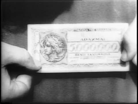 Man holding picture of Churchill / men and women exchanging money for bread / close up of monetary paper / rich woman in crowd gives away money