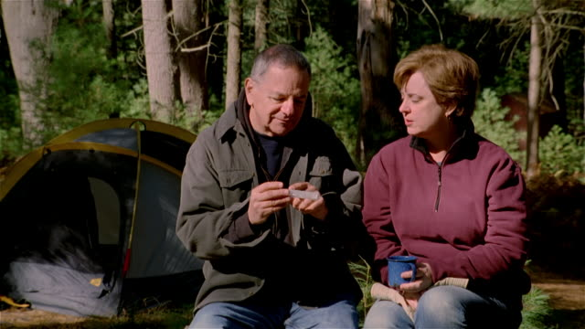 CU, man holding pill box talking to woman sitting at camp site, USA, Pennsylvania, Solebury