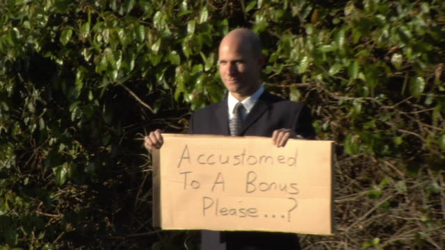 ms man holding sign saying 'accustomed to a bonus...please' on street, los angeles, california, usa - 風刺点の映像素材/bロール