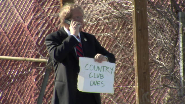 MS TD TU Man holding sign saying 'Country Club Dues' and talking on mobile phone on street, Los Angeles, California, USA