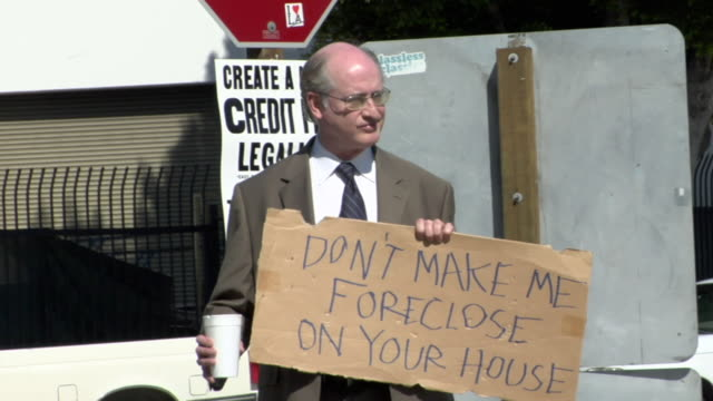 zi ms man holding sign saying 'don't make me foreclose on your house' on street, los angeles, california, usa - see other clips from this shoot 1458 stock videos and b-roll footage
