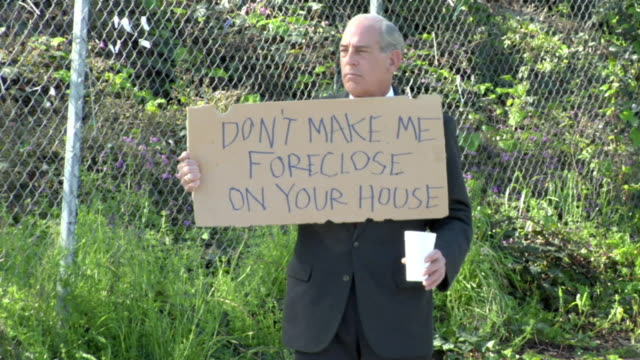 MS Man holding sign saying 'Don't Make me Foreclose on your House' on street, Los Angeles, California, USA