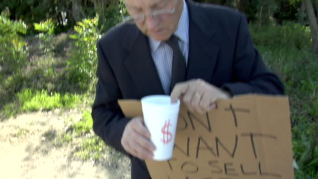 vídeos de stock, filmes e b-roll de  man holding sign saying 'don't want to sell aspen' and disposable cup with money, los angeles, california, usa - sátira
