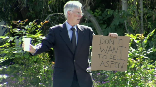 ms pan man holding sign saying 'don't want to sell aspen' on street, los angeles, california, usa - see other clips from this shoot 1458 stock videos and b-roll footage