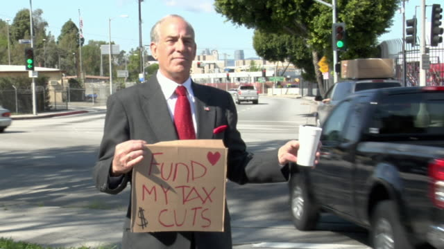 ms man holding sign saying 'fund my tax cuts' on street, los angeles, california, usa - recession stock videos & royalty-free footage