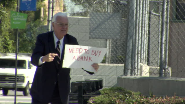 ms man holding sign saying ''need to buy a bank' on street, los angeles, california, usa - 2009 video stock e b–roll