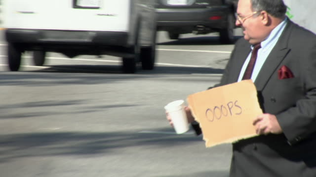 ms zo ws man holding sign saying 'oooops' on street, los angeles, california, usa, zi - crisis stock videos & royalty-free footage