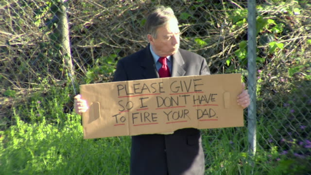 ms man holding sign saying 'please give so i don't have to fire your dad' on street, los angeles, california, usa - 2009 video stock e b–roll