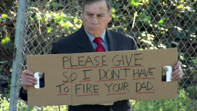 ms zo man holding sign saying 'please give so i don't have to fire your dad' on street, los angeles, california, usa - satire点の映像素材/bロール