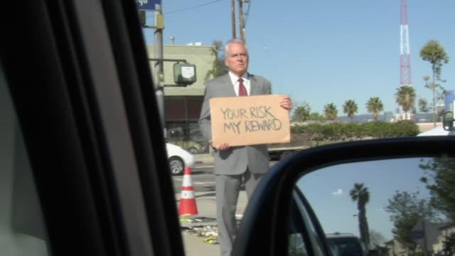 vídeos de stock, filmes e b-roll de ms shaky man holding sign saying 'your risk my reward' on street, los angeles, california, usa - sátira