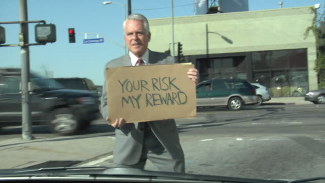MS Man holding sign saying 'Your Risk My Reward' on street, view from car, Los Angeles, California, USA