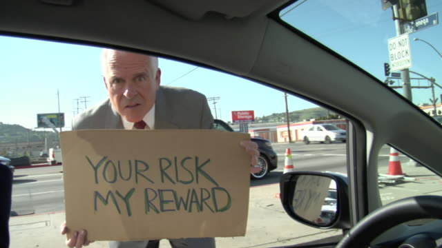 ms shaky man holding sign saying 'your risk my reward' on street, view from car, los angeles, california, usa - 2009 video stock e b–roll