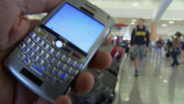 CU Man holding smart phone at busy airport baggage claim /  Atlanta, Georgia, USA
