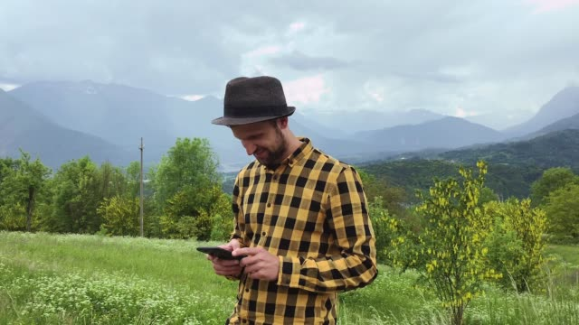 man holding smart phone in landscape - one mid adult man only stock videos & royalty-free footage