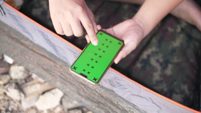 vídeos de stock, filmes e b-roll de homem que prende o telefone esperto com a tela verde mock-up na barraca de acampamento - modelo web
