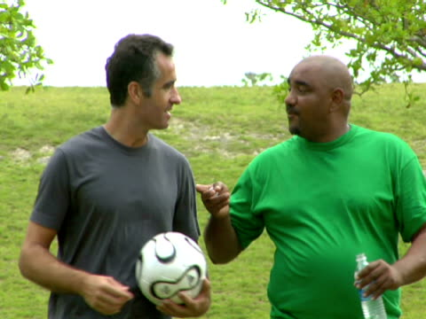 cu,  man holding soccer ball talking to colleague walking through park,  miami,  florida,  usa - body positive stock videos & royalty-free footage