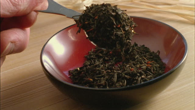 slo mo, cu, man holding spoon with earl grey tea leaves, close-up of hand - dried tea leaves stock videos & royalty-free footage