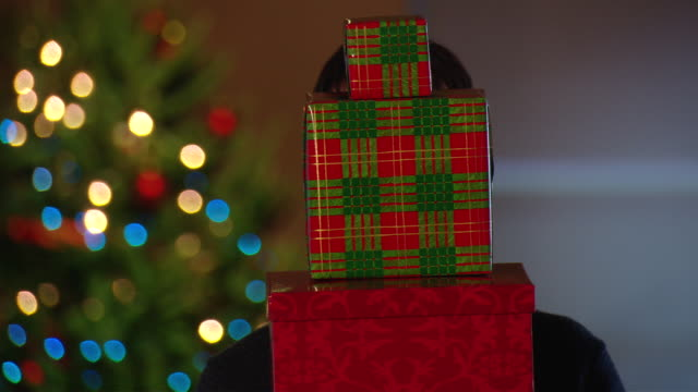 cu man holding stack of gifts near christmas tree, then lowers them and smiles / new york, usa - stapeln stock-videos und b-roll-filmmaterial