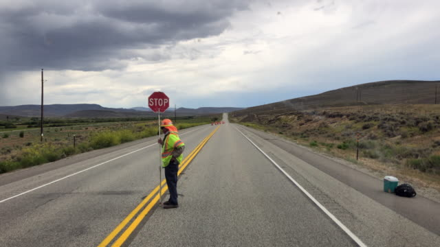 stockvideo's en b-roll-footage met man holding stop sign at a road construction site in colorado amid the 2020 global coronavirus pandemic - stopbord